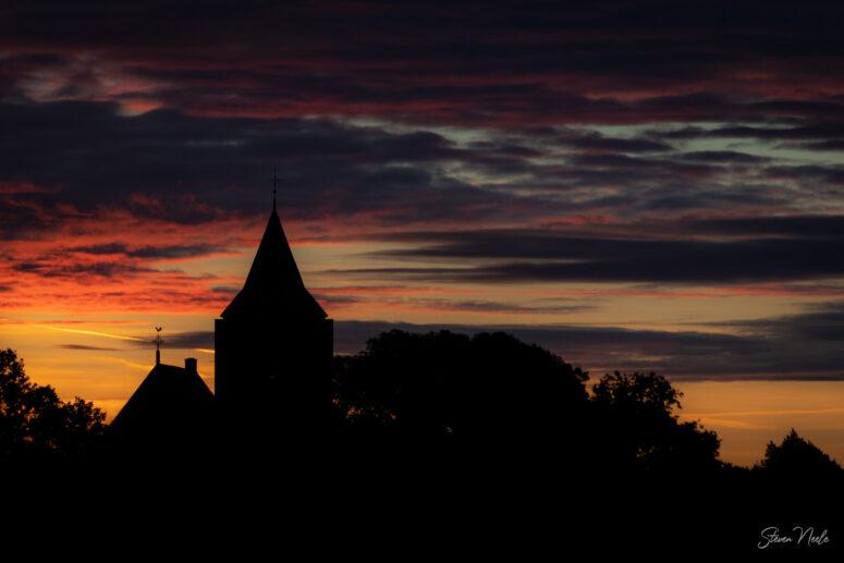 Kerktoren bij zonsondergang